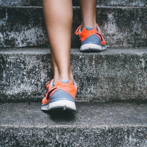 Woman's feet wearing trainers walking up steps